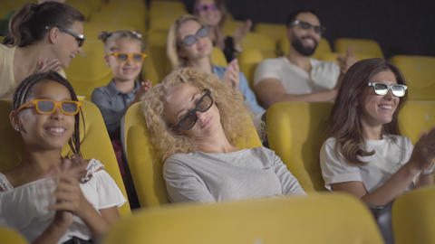 Angle view of sleeping Caucasian woman in 3d glasses sitting in cinema as people Live Action