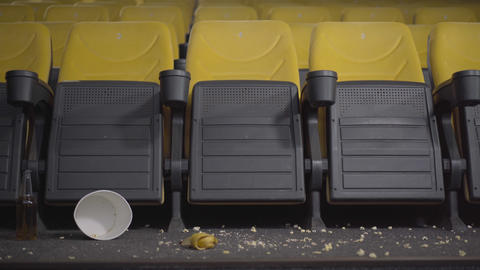 Camera moves along dirty empty cinema with yellow chairs. Movie theater with Live Action