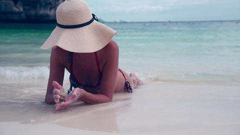 Beautiful woman on holiday relaxing lying on the beach wearing straw hat Live Action