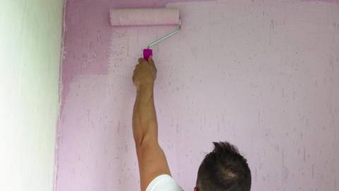 Close-up of a man paints the top of the wall pink Live Action