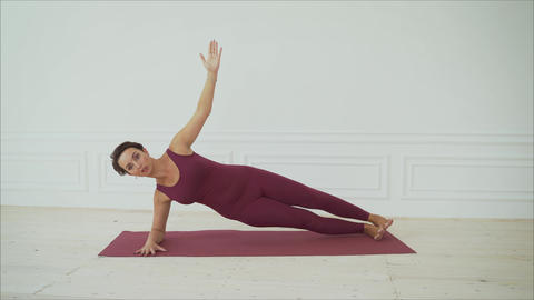 Young woman shows pilates exercises. Young attractive woman practicing yoga at Live Action