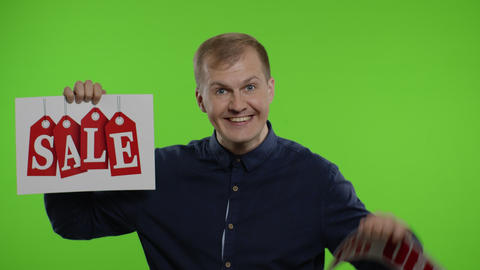 Cheerful man showing Sale word and showing Up To 70 percent Off inscription Live Action