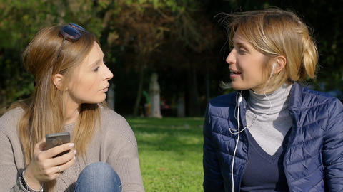 two female friends listen to the music with earphones and smartphone Footage