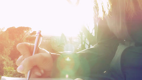 young woman writing on a notepad in the park at the sunset Footage