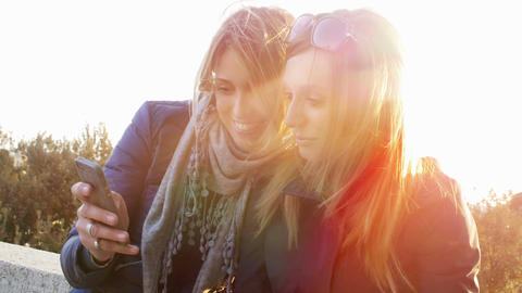 making a selfie at the sunset: two female friends taking pictures Footage