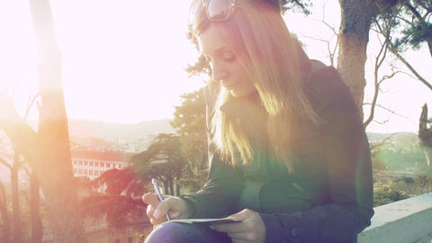 young woman writing on the diary at the sunset; flare in camera Footage