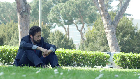lost and confused businessman on the grass: sad and depressed businessman Footage