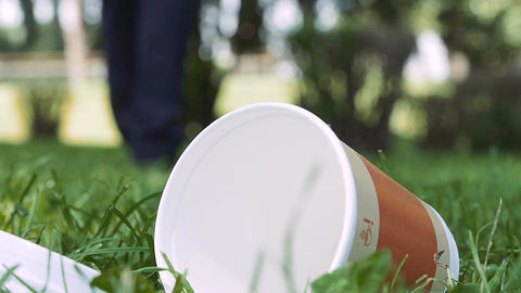 throw trash in the park: man throws away a glass coffee takeaways Live Action