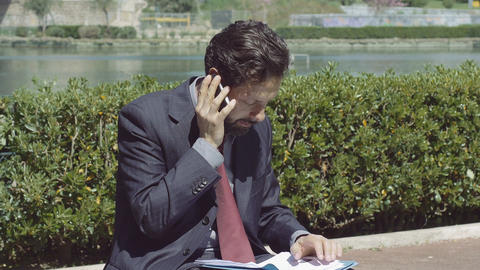 businessman working outdoor with his smartphone and documents Footage