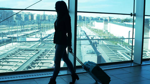 young woman walking with a trolley suitcase and train tracks in background Footage