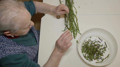 old woman preparing asparagus: peeling asparagus Live Action