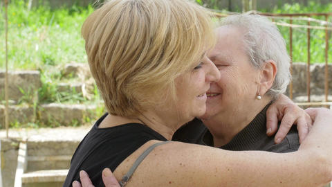 two smiling women embracing: old mother and daughter Live Action