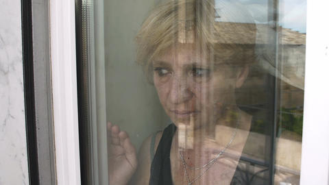 mature woman at the window: thoughtful woman behind the window Footage
