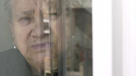 sad and old woman rear the window: pensive old woman looking out the window Live Action