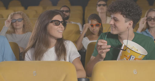 Portrait of happy young couple discussing film in cinema. Cheerful Caucasian Live Action