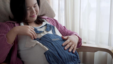 Happy pregnant woman and expecting baby at home Live Action