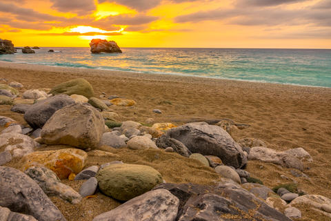 Sunset Over the Sea and Colorful Stones on a Sandy Beach Fotografía