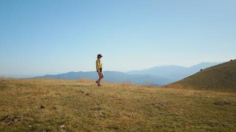 Hipster woman walk on mountain peak in sunshine Live Action