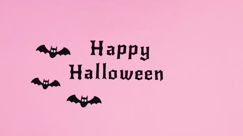 Bats fly around Happy Halloween text on pink theme. Stop motion Animation
