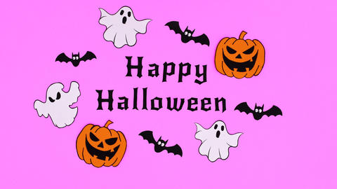 Pumpkins, ghosts and bats fly around happy Halloween text. Stop motion Animation