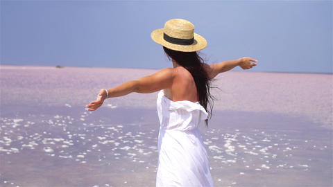 Woman in hat walk on a pink salt lake on a sunny summer day Acción en vivo