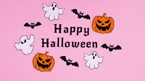 Pumpkins, ghosts and bats fly around happy Halloween text . Stop motion Animation