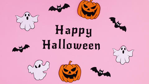 Ghosts, pumpkins and bats appear around Happy Halloween text. Stop motion Animation