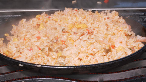 UHD closeup shot of the rice being stir fried with an egg, shrimps and vegetables Live Action