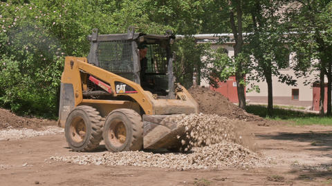 Skid steer loader moving sand soil at construction area outdoors Live Action