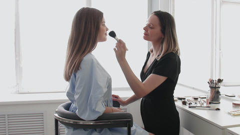 Professional make-up artist and young model are looking at the camera Live Action