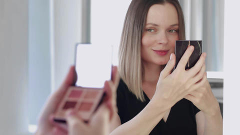 Young woman looking in a small mirror and smiling Live Action