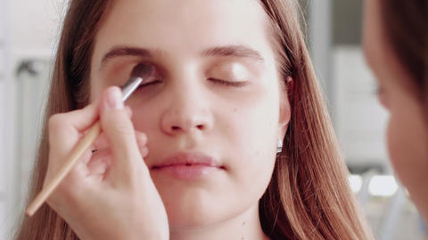 Professional make up artist makes blush on model's face using makeup brush Live Action