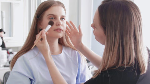 Make up applying. Face powder, facial makeup. Rouging young attractive girl Live Action