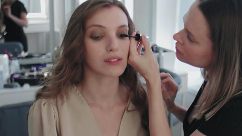 Process of Professional Makeup for beautiful and young woman sitting at the Live Action