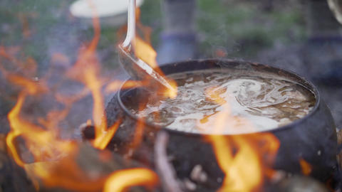 A pot of soup cooked over a fire. Stir soup with soup ladle, which is cooked in Live Action