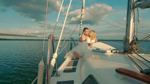 Brides sit on a yacht, looking at each other. Beautiful landscape behind them Live Action