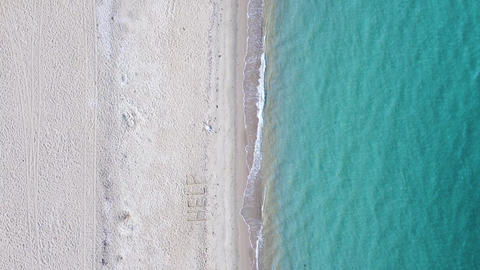 Blue clear sea and SOS message on sand beach. Help written on sand beach. Aerial view Live Action