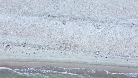 Sand beach with Help SOS message and turquoise clear sea. Aerial view Live Action