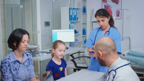 Doctor and nurse talking with child patient Live Action
