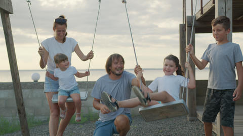 Happy family rolls young children on a swing outdoors at sunset Live Action