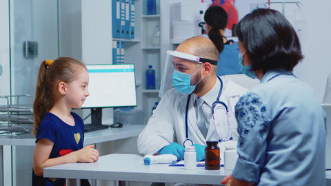 Cheerful pediatrician smiling at little girl Live Action