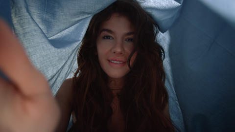 POV pretty woman looking camera under sheet. Smiling lady sitting below cloth Live Action