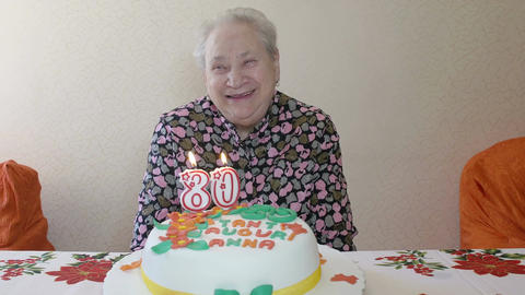 elderly woman birthday: old woman blows out the candles on the cake Footage