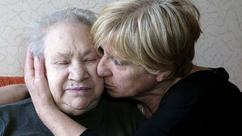 sad old woman comforted by her daughter in their house Footage