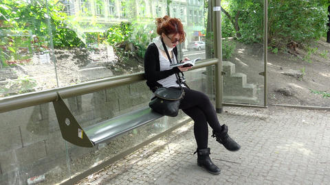 young woman reading the tourist guide at the bus stop in Prague Footage