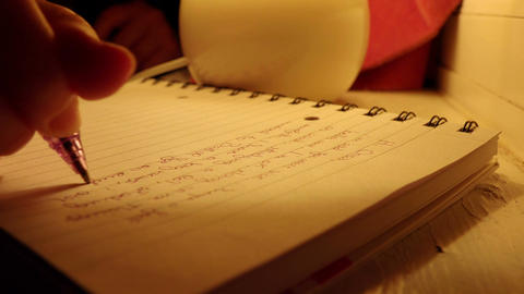female hand writes in the night with the light of a small table lamp Footage