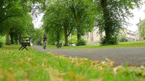 A woman riding a bike in slowmotion Footage