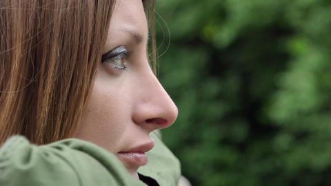Pensive young woman in the park behind the trees background Live Action