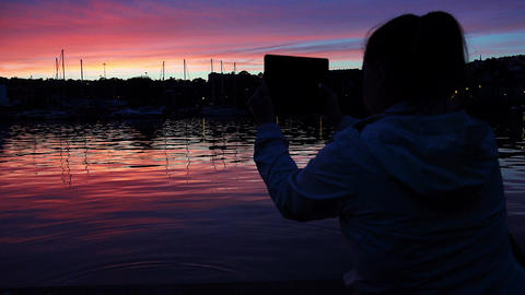 iPad, tablet computer: woman making photos of the sunset on the river Footage
