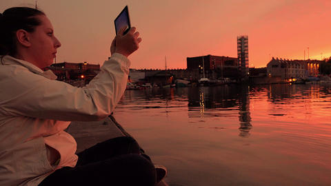 making photos with a tablet computer at the sunset: woman on the riverside Footage